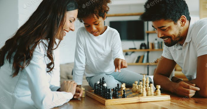 Happy family playing chess together at home
