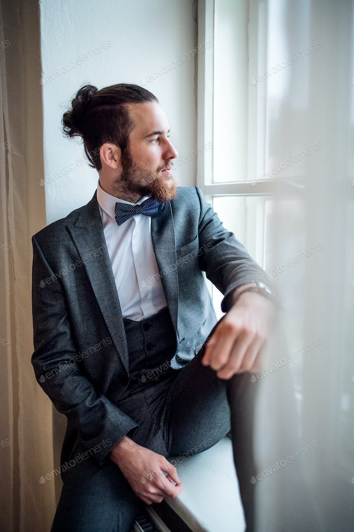 A handsome hipster young man with formal suit sitting on a window sill on an indoor party.
