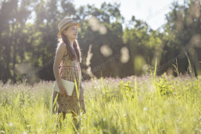 A child in a straw hat walking through long grass carrying a book.