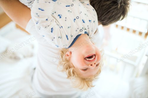 Father holding a happy toddler boy upside down.
