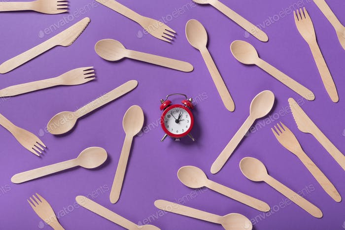 Many wooden spoons and forks on purple background, top view