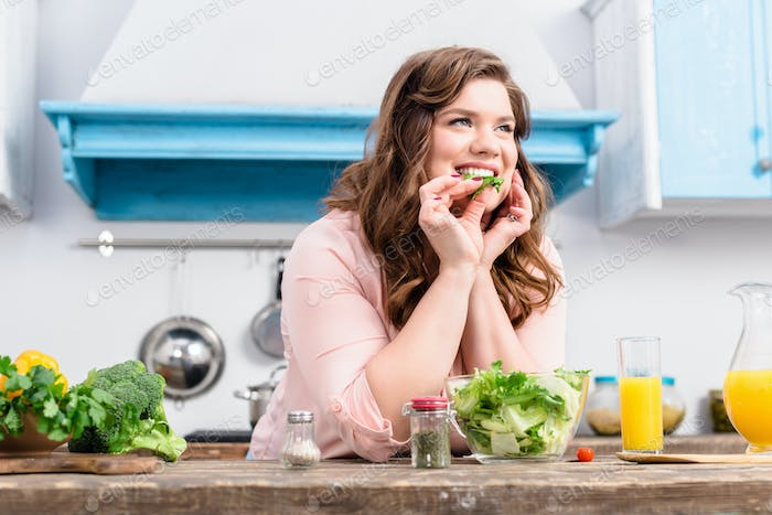 overweight smiling woman at table with fresh salad in kitchen at home