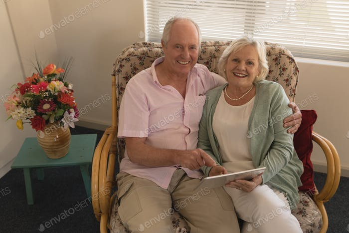 Senior couple using digital tablet and looking at camera in living room at nursing home