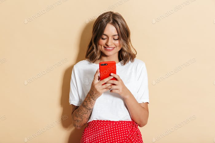 Image of pretty woman in red skirt smiling and holding smartphone