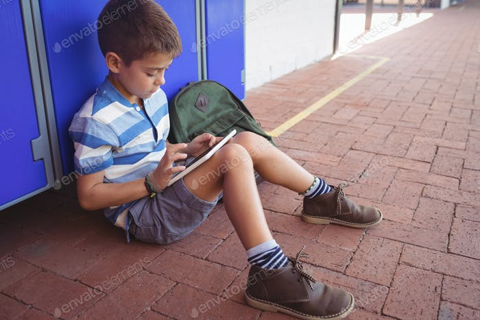 Boy using digital tablet while sitting by locker