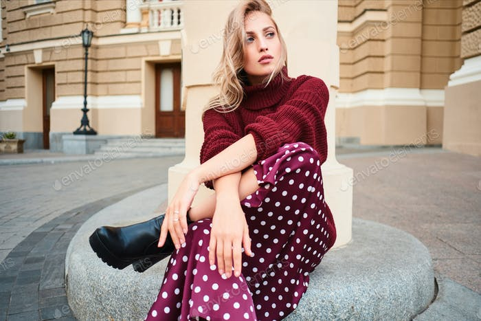 Gorgeous stylish blond girl in knitted sweater sensually looking away posing outdoor