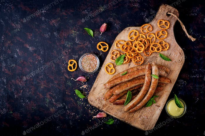 Pretzels and grilled sausages on dark background. Oktoberfest. Flat lay. Top view