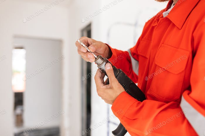 Close up builder in orange work clothes holding drill machine in