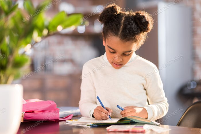 african american schoolgirl doing homework, elementary school student concept