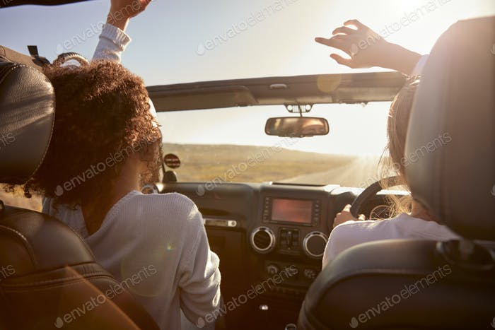 Young adult girlfriends driving with sunroof open, back view