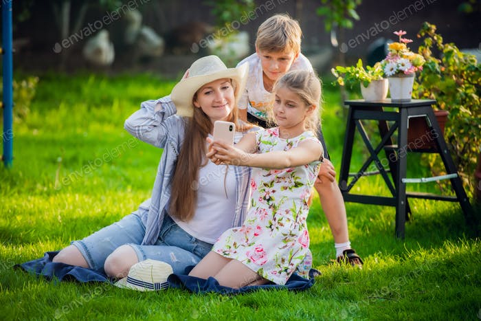 Young mother with pretty daughter and handsome son make photo in backyard