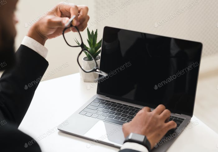 Cropped image of businessman using laptop with blank screen