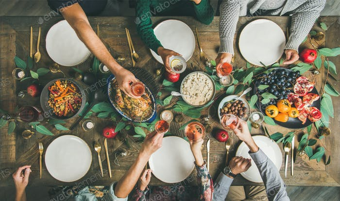 Flat-lay of friends or family feasting at festive table