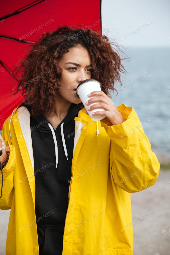 Concentrated african curly young lady walking outdoors and drinking coffee.