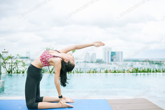 Asian fit woman exercising at the poolside