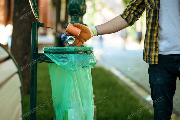 Young man puts garbage in plastic bag in park