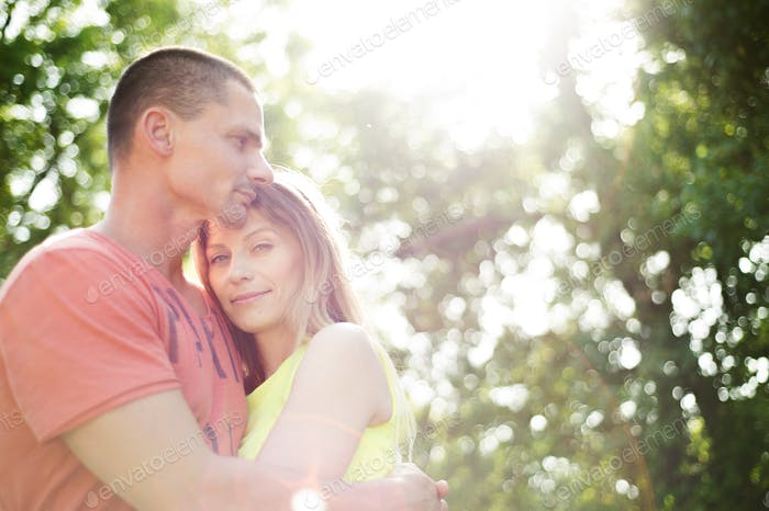 Beautiful young couple in love. Sunny summer nature.