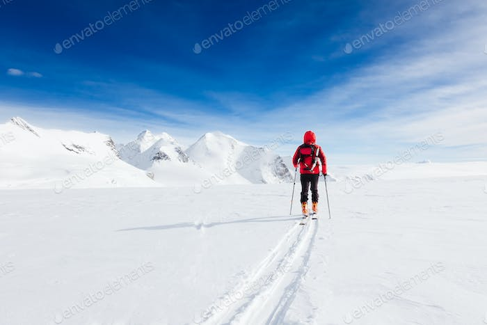 Mountaineer walking on a glacier during a high-altitude winter expedition in the european Alps.
