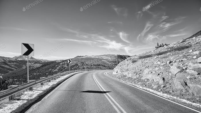 Black and white picture of a mountain road turn
