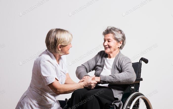 Studio portrait of a senior nurse and an elderly woman in wheelchair.