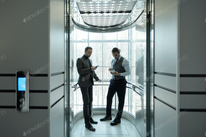 Two young elegant office managers scrolling in mobile gadgets