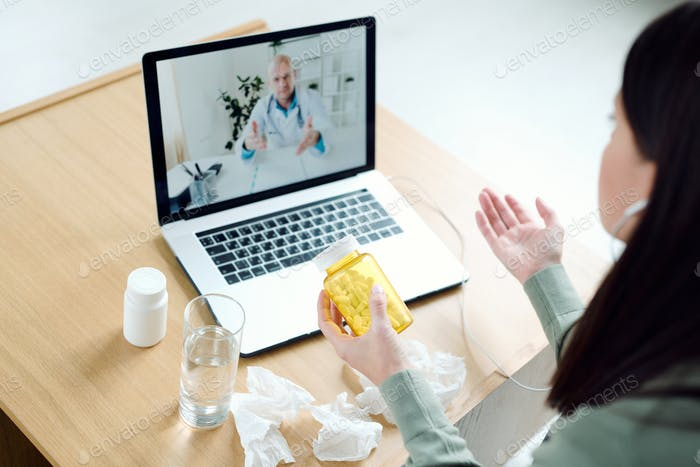 Mature male doctor on laptop display giving medical recommendations to patient