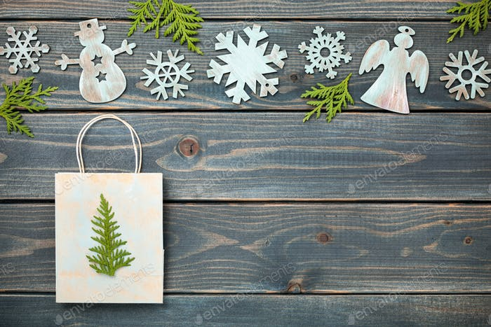 Christmas decoration and gift bag on wooden background