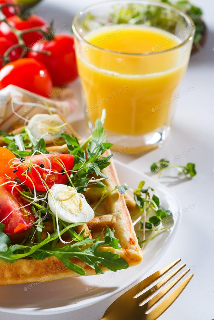 Served breakfast with savory waffles, boiled egg, tomato and microgreen on light background