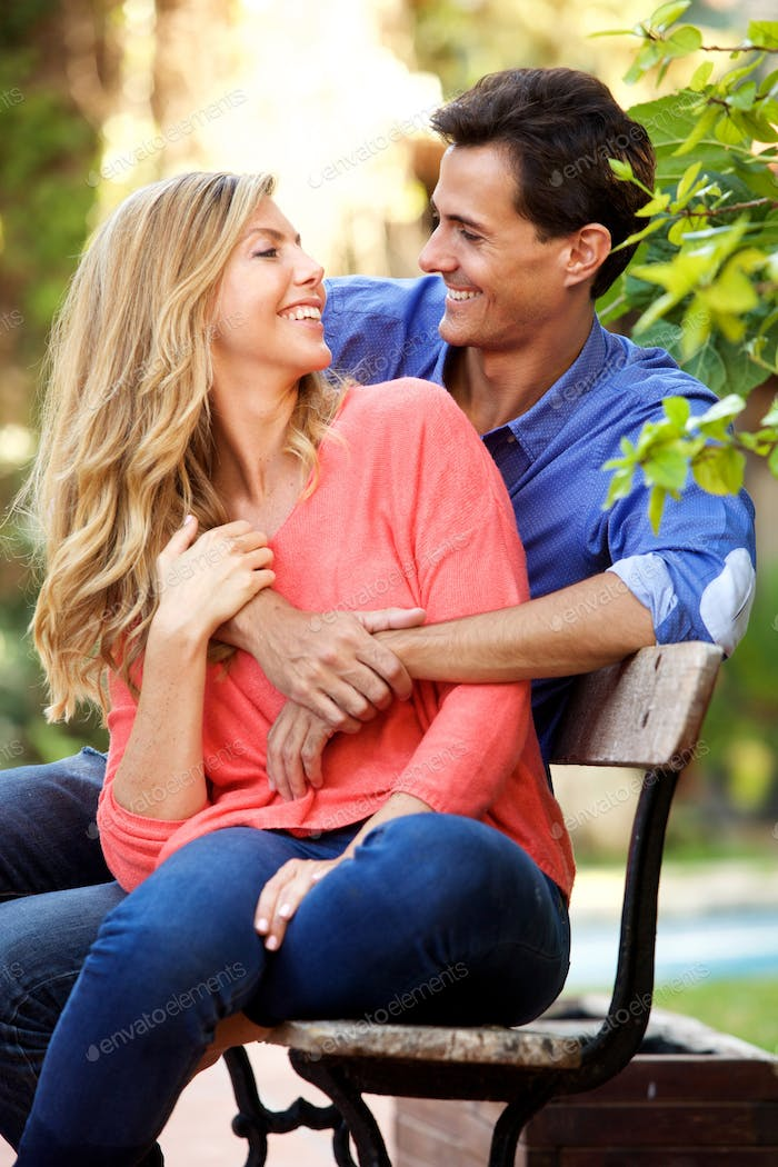 happy boyfriend and girlfriend sitting together on bench laughing