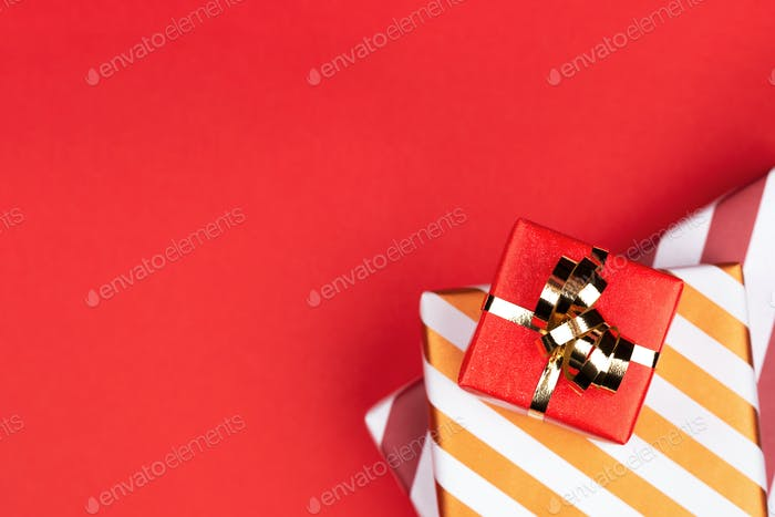 Red and Striped Gift Boxes on Red Background with Golden Bow