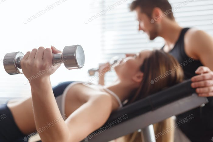 Woman lying with dumbbells