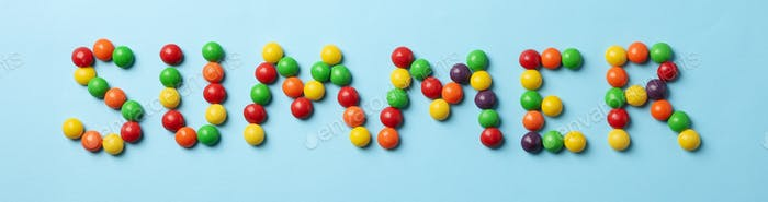 Palabra de verano hecha de caramelos sobre fondo azul, vista superior