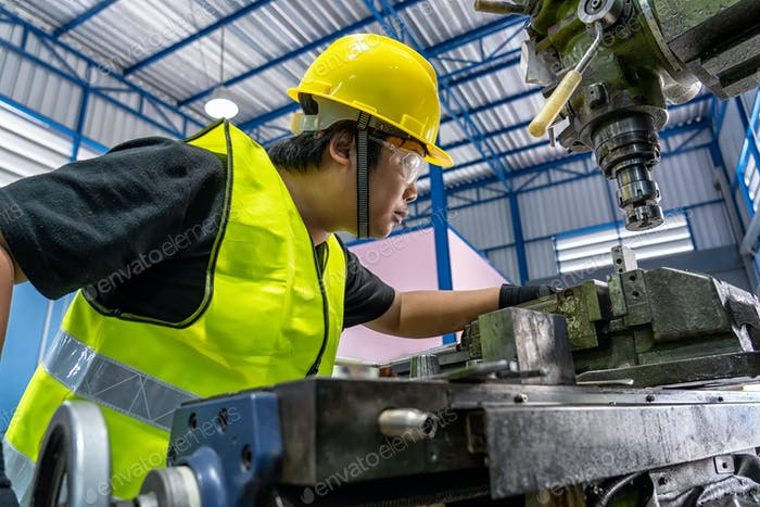 Asian machinist in safety suit operating the professional lathes in metalworking factory