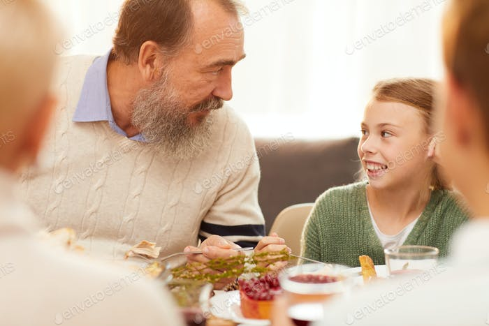 Grandfather and granddaughter at the table