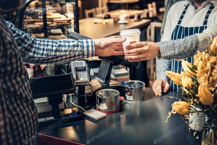 Un hombre vendiendo café a un consumidor en una cafetería.