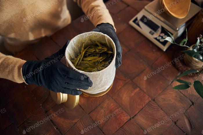 Male worker hands holding jar of tea leaves