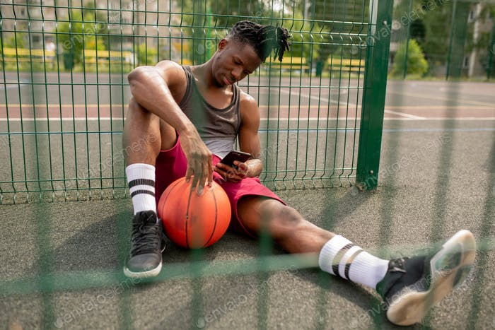 Young African basketball player with smartphone relaxing by fence of playground
