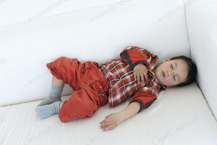 Two year old boy sleeping on a couch