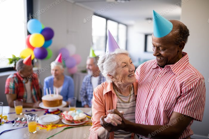 Happy senior couple wearing party hats with friends