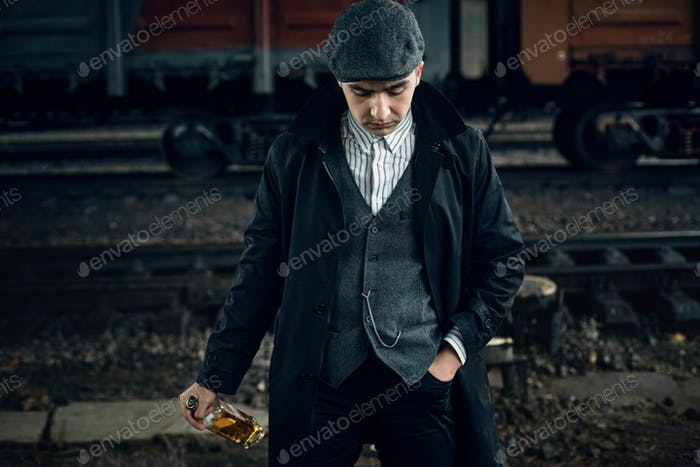 Stylish gangster man with bottle whiskey in retro look