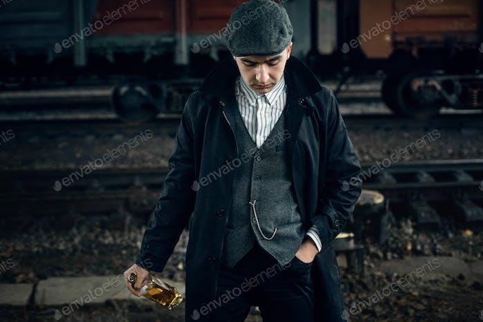 Стильный гангстер мужчина с бутылкой виски в ретро вид