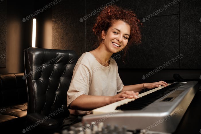Young attractive woman happily looking in camera playing on electric piano in sound recording studio