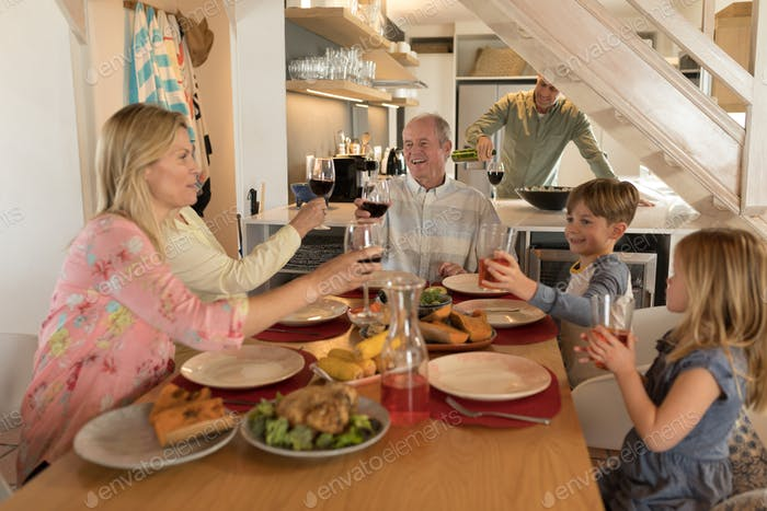 Side view of a multi-generation family having wine on dining table at home