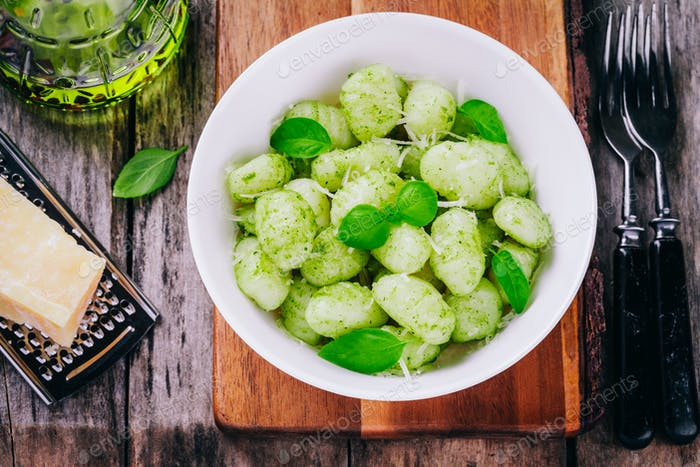 Italian food: homemade gnocchi with pesto sauce, parmesan and basil