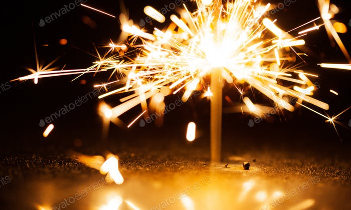 Close-up of golden blurry sparks burn in the dark