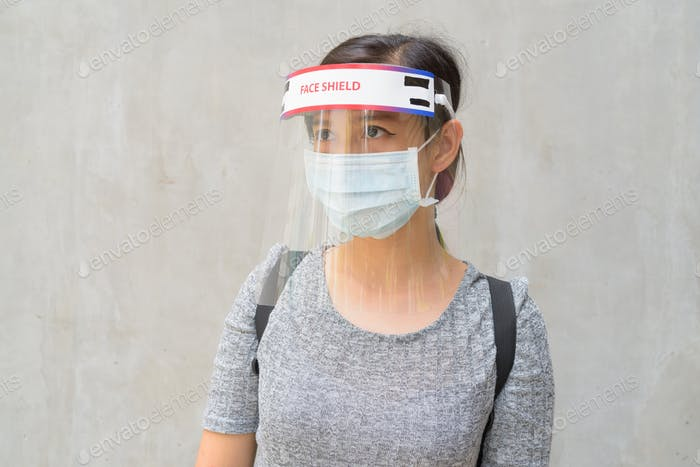 Young Asian woman thinking with mask and face shield for protection from corona virus outbreak