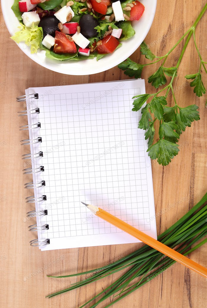Greek salad with vegetables and notepad for notes, healthy nutrition