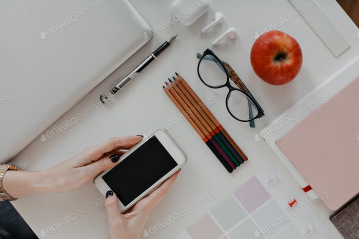 Flat lay. Womans hands holding iPhone on background of pencils, glasses, MacBook
