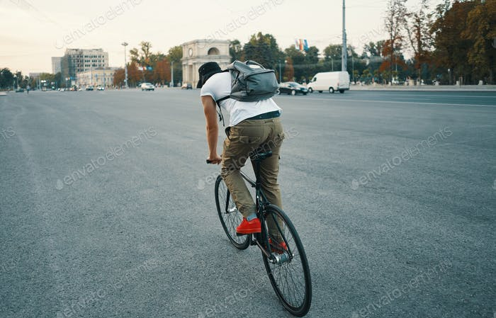 Young modern man cycling on a classic bike on the city road with