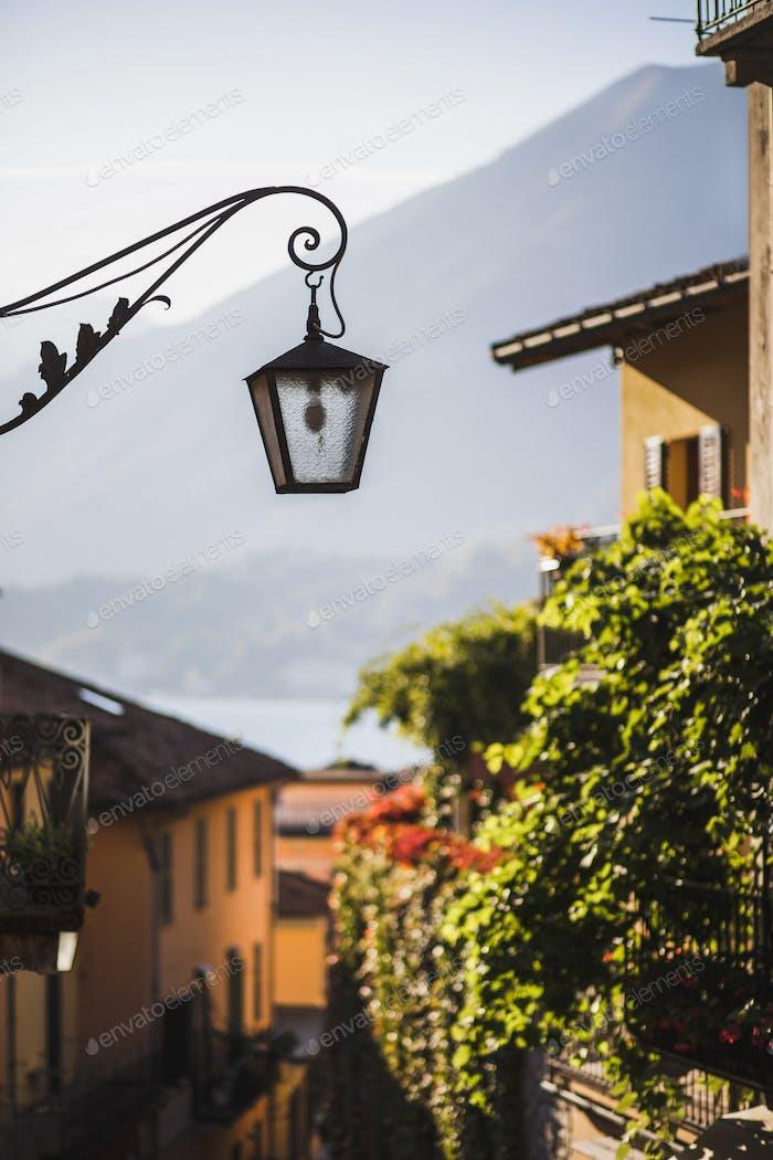 Antiguo farol forjado de metal en una acogedora calle europea. Detalles arquitectónicos de la ciudad antigua. Verano en Italia.
